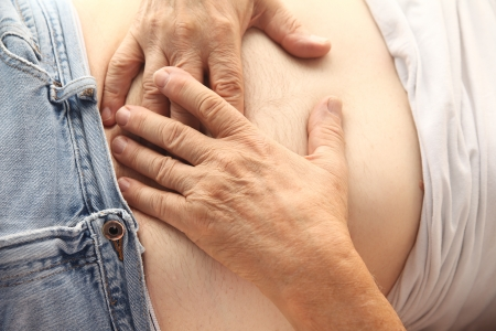 a reclining man holds both hands to his abdominal area