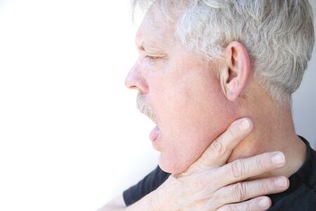 gasping: senior with mouth open and hand on jaw and neck