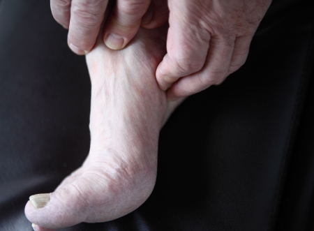 man s hands on his painful foot photo