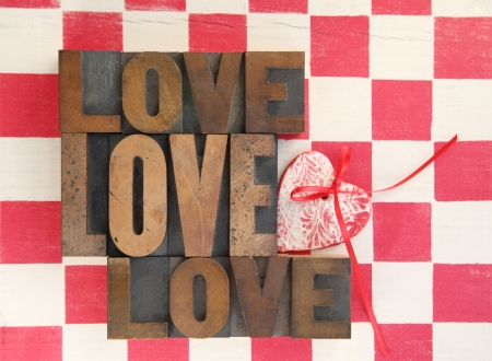 the word love repeated three times with a handmade heart ornament on a checkerboard Stock Photo