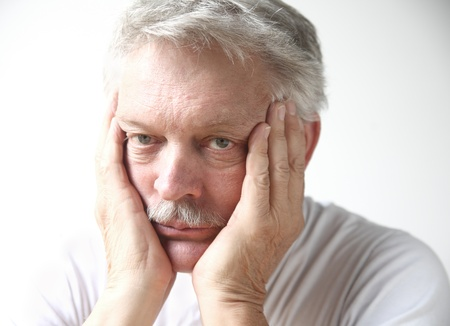 bored man: senior man rests his face in his hands and looks disappointed or bored Stock Photo
