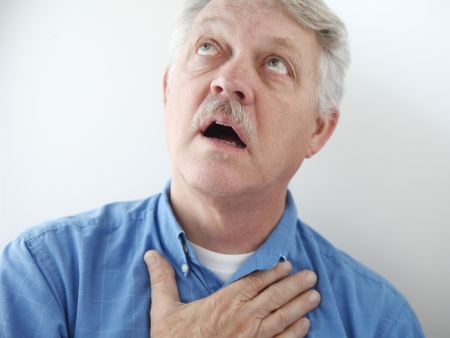 reverent: older man gazes skyward with a hand on his chest
