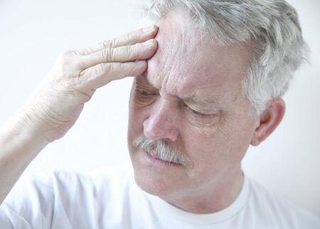 older man puts his fingers against his forehead while frowning in pain Stok Fotoğraf