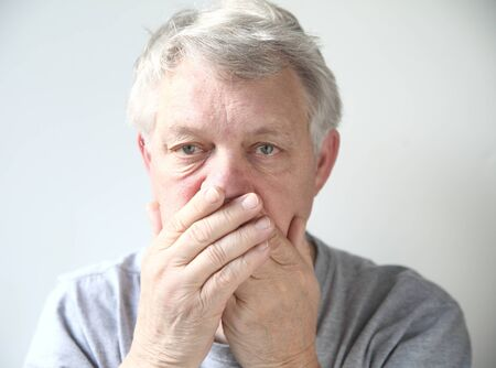 halitosis: senior man holds his hands over his mouth