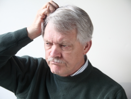 scratching head: senior man with frustrated, puzzled expression scratches his head