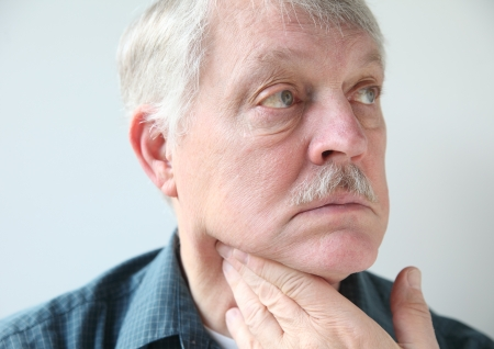 senior man on a neck pain: older man with a sore throat or neck Stock Photo