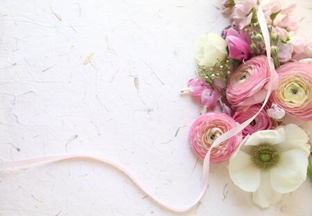 ranunculus, anemones, stock and bleeding heart flowers with a pink ribbon on texture