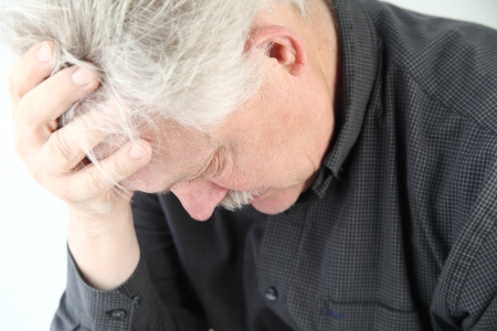 slumped: senior man bent over with grief or depression Stock Photo