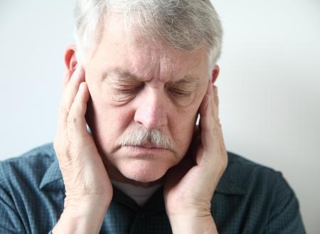 dolor de oido: hombre mayor que tiene ambas manos en la mandíbula superior, cerca de los oídos