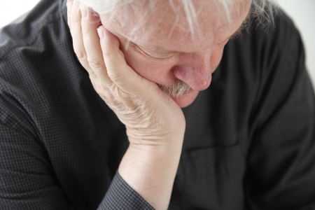 slumped: older man slumped in depression or grief