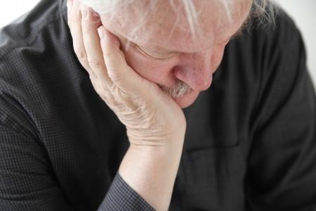 slumped: older man slumped in depression or grief