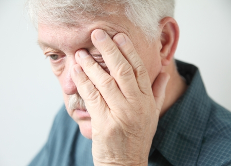 overworked senior rubs an eye in fatigue