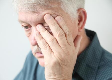 hand rubbing: overworked senior rubs an eye in fatigue