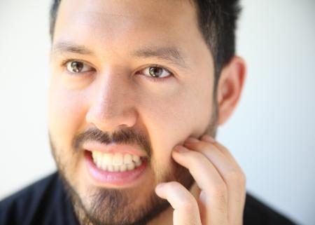 young man scratches his facial hair photo