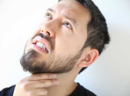 sore throat: bearded thirty-year old man has pain in his throat