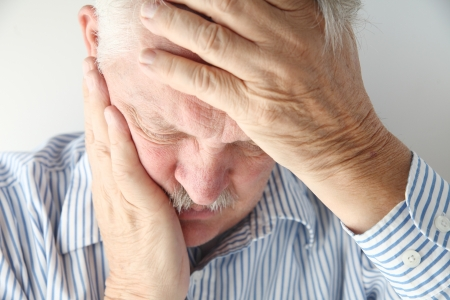 older man in pain holds his head with both hands