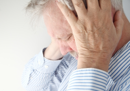 senior health: stressed older man holds his head in both hands