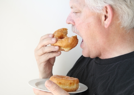 senior man enjoying unhealthy food photo