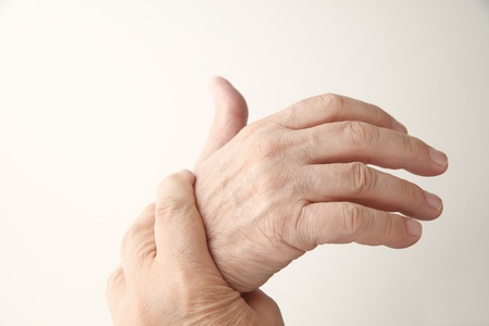 senior man holds his aching hand