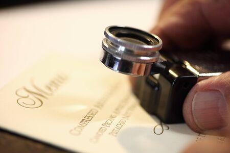 control de calidad: hombre usa una lupa para mirar de cerca su trabajo Foto de archivo
