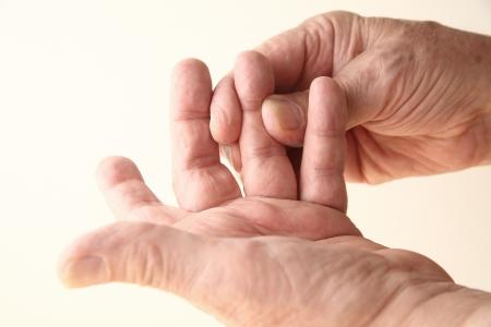 senior man met stijfheid of gevoelloosheid in zijn vinger