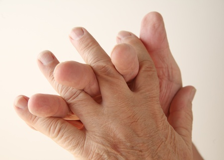 joining hands: an older man crosses the fingers of one hand with the other