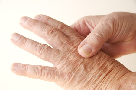 soreness: senior man massages the pain on a knuckle
