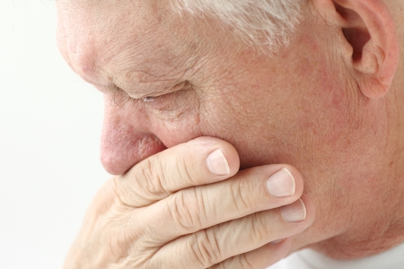 queasy: nauseated mature man holds hand up to mouth