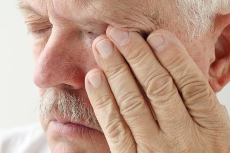 senior man heeft vermoeide ogen en vermoeidheid