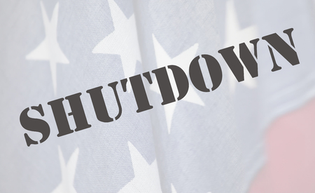current events: the word shutdown in a stencil font on an old USA flag