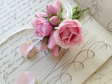 penmanship: small bunch of fresh roses tied with ribbon on vintage pages with penmanship flourishes