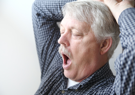 tired senior man stretches and yawns Banque d'images