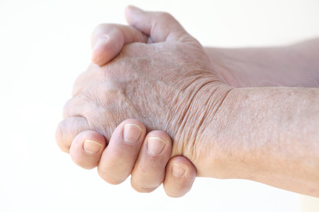 clasps: senior man clasps his hands together