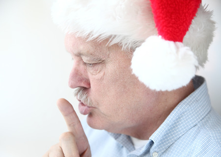 older man makes a shushing gesture with his index finger Stock Photo