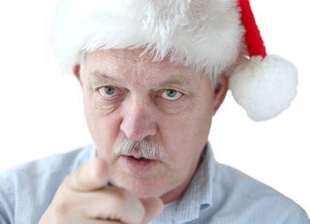 admonish: senior man wearing Christmas hat points finger at viewer