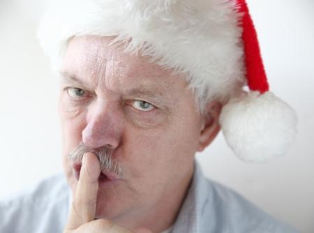 shushing: senior man makes shushing gesture