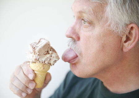 finger licking: senior man ready to enjoy a cold treat