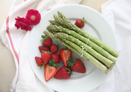 fresh bunch of asparagus with strawberries and flowers Stock Photo