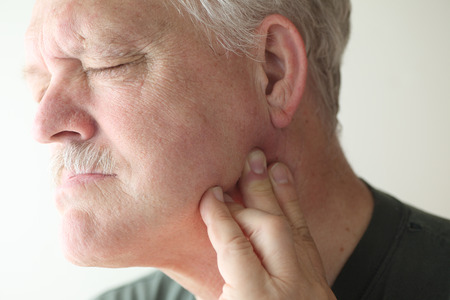 pain: senior man suffering from pain in his jaw
