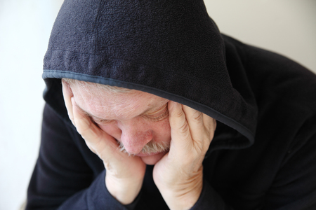slumped: Senior man wearing a dark hoodie slumps in depression   Stock Photo