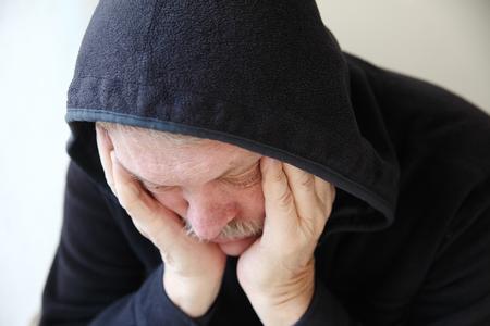 slumped: Senior man wearing a dark hoodie slumps in depression   Stock Photo