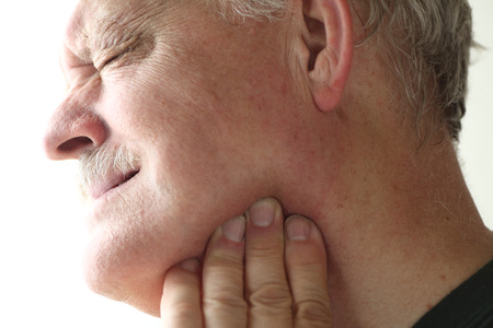 senior man with soreness in his jaw area Stock Photo