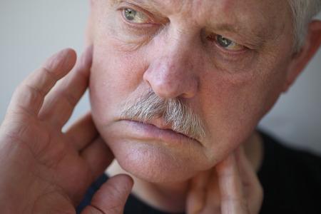 Senior man touches his sore jaw area  Stock Photo