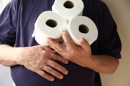 Man with hand over his stomach holds three rolls of toilet paper.