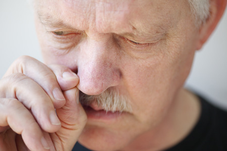 tries: Older man tries to relieve his stopped up nostril  Stock Photo