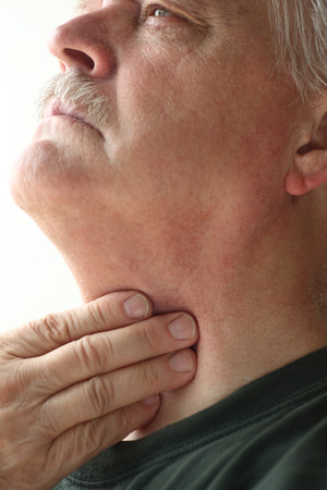 Older man has a problem with swallowing or a sore throat photo