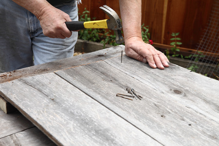 A man reuses old nails to hammer together weathered boards. Banco de Imagens