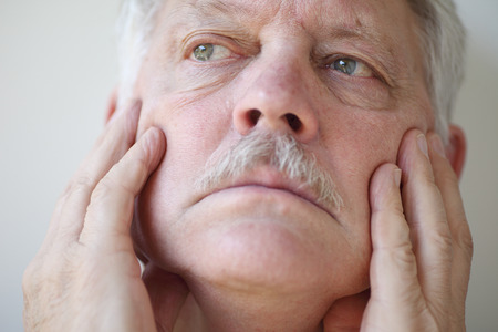 neuralgia: An older man has his hands on his cheeks and a thoughtful expression.