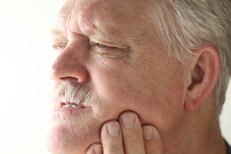 head pain: Senior man shows area of pain on his jaw with his fingers.