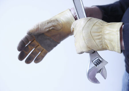 A man holds a wrench while putting on his work gloves. photo